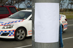 Law & Order Notice. Empty bill poster on light pole with police squad car in the background stock images