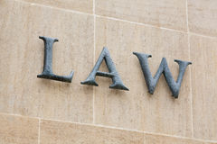 Law sign. Letters spelling the word law L A W on a brown stone wall Stock Photo