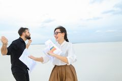 Law students man and woman rejoice at passing exams dancing. Future lawyers male and female come to seaside to have rest after passing exams, girl with ponytail Stock Photography