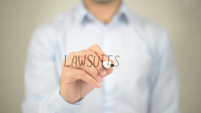 Law Suits, man writing on transparent screen royalty free stock photography