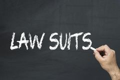 Law suits words written on the blackboard. Male`s hand writing text on the chalkboard: Law suits royalty free stock photos