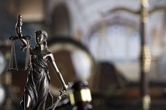 Law symbols in the old university library. Themis - statue of justice, scale, judge`s gavel and books. Library background royalty free stock image
