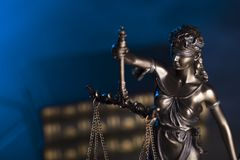 Law theme. Blind justice symbol - Themis. Law code. Statue of justice and  books. Blue background. Place for text Royalty Free Stock Photos