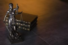 Law theme. Blind justice symbol - Themis. Law code. Statue of justice and  books. Brown background. Place for text Royalty Free Stock Image