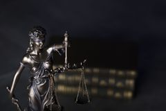 Law theme. Blind justice symbol - Themis. Law code. Statue of justice and  books. Dark  background. Place for text Stock Photos