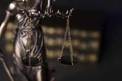 Law theme. Blind justice symbol - Themis. Law code. Statue of justice and  books. Dark  background. Place for text Royalty Free Stock Image