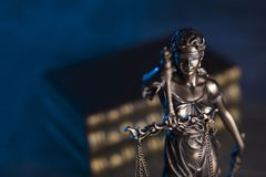 Law theme. Blind justice symbol - Themis. Law code. Statue of justice and  books. Dark blue background. Place for text Royalty Free Stock Image