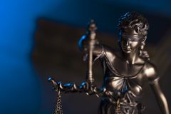 Law theme. Blind justice symbol - Themis. Law code. Statue of justice and  books. Dark blue background. Place for text Royalty Free Stock Photo