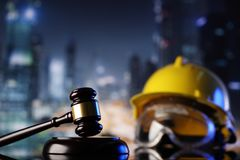 Construction law. Law theme. Construction law`s symbols  - helmet and gavel. Constuction background Stock Image