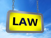 Law on billboard. Law on yellow light box billboard on blue sky background Royalty Free Stock Images