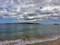 Lawa koral z kiścią rozbijać przy Maluaka plażą, skała i Kihei Maui z niebem i chmurami Zdjęcie Stock