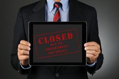 Lawmaker Holding Tablet Computer with Closed Message. Closeup of a Congressman holding a tablet computer in front of his torso with the Closed Due to Government Royalty Free Stock Photo