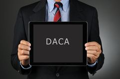 Lawmaker Holding Tablet Computer with DACA Message. Closeup of a Congressman holding a tablet computer in front of his torso with the acronmy DACA Royalty Free Stock Image