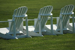 Lawn. A row of three white, wooden  lawn chairs on a vividly green lawn Royalty Free Stock Image