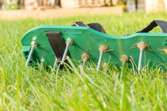 Lawn aerating shoes with metal spikes. Used to improve the quality of the grass growth. Closeup of the green shoe with its spikes and screws Royalty Free Stock Images