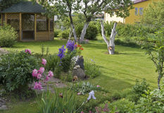 Lawn, arbour and flower bed. Lawn; arbour and flower bed in a court yard of the rural house Royalty Free Stock Photography
