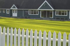 Lawn bowling clubhouse. Focus on white picket fence with green lawn and clubhouse in background Royalty Free Stock Photo