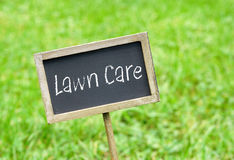 Lawn Care - chalkboard on green grass background. Lawn Care in the garden - chalkboard with text on green grass background stock photo