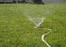 Lawn care irrigation system at works on green grass stock photos