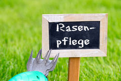 Lawn care. Sign with the german words Lawn care stands on the green lawn stock photography