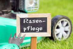 Lawn care. Sign with the german words Lawn care stands on the green lawn stock photos