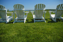 Lawn Chairs. A row of four lawn chairs facing out toward the lake Royalty Free Stock Photography