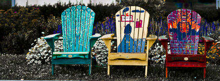 Lawn chairs in front of a flower bed. Stock Photos