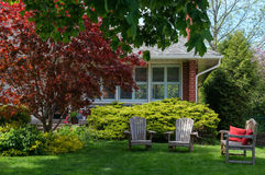 Lawn Chairs in front of a House. Three chairs on a lawn in front of a house, red maple tree stock image