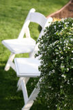 Lawn chairs in the grass. Two white lawn chairs sitting in the grass next to flowers Stock Photo