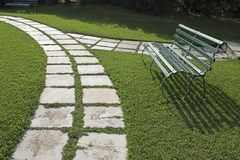 Lawn chairs on green grass. In garden with curved walkway stock image