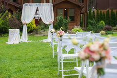 Lawn with chairs for the wedding ceremony. Several white chairs standing on a green lawn in front of house. White chairs decorated with bouquets of flowers and Royalty Free Stock Images