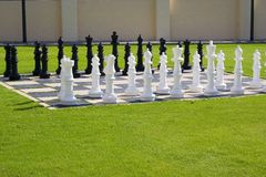 Lawn Chess Set. A life-size chess set is layed out on tiles surrounded by a green lawn Stock Photo