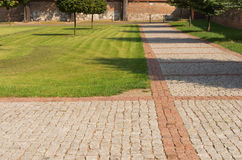 Lawn with a cobbled path in the park. Green lawn with a cobbled path in the park Royalty Free Stock Photo