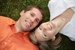Lawn Couple 2. Happy young couple smiling and lying on the grass Royalty Free Stock Images