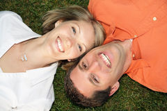 Lawn Couple. Happy young couple laughing and lying on the grass Stock Images