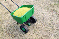 Lawn fertilizer. In Lawn spreader on grass Royalty Free Stock Photography