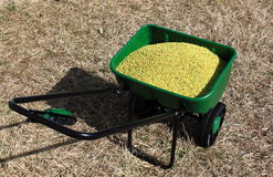 Lawn Fertilizer Spreader. Green Lawn fertilizer spreader on dried lawn at the very early spring Royalty Free Stock Images
