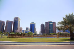 Lawn in front of Abu Dhabi tall buildings. Royalty Free Stock Photography