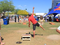 Lawn Game: Cornhole - Pitching The Bag. Picture taken (at 100°F/38°C) during the annual Salsa Challenge in Tempe, Arizona/USA (Beach Park): A young man is stock image