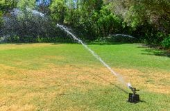 Lawn irrigation sprinkler on a green lawn. royalty free stock photos