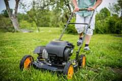 Lawn mover and man. Lawn mover cutting grass in garden, man half seen Royalty Free Stock Photo