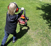 Lawn moving. Blond boycutting grass with a lawn mover Royalty Free Stock Photo