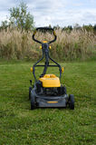 Lawn mower. Yellow lawn mower on the green field Stock Images
