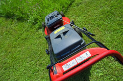 Lawn mower. Red lawn mower in the garden Stock Photography