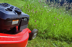 Lawn mower. Red lawn mower in the garden Royalty Free Stock Photography