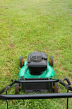 Lawn mower. Lawn mover on green grass ready to start mowing Royalty Free Stock Image