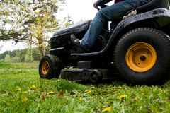 Lawn mower. Worker mowing with black riding lawn mower Stock Photography
