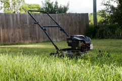 Lawn Mower in Backyard Stock Images