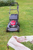 Lawn mower and a bag of cut grass on the green lawn Stock Image