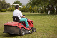 Lawn mower cutting grass Stock Photos